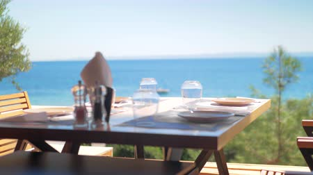 pohárek : Served table in outdoor cafe with bright blue sea in background. Shot with changing focus