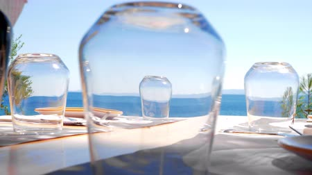 pohárek : View to the bright blue sea through the clear empty glasses on served table in outdoor cafe on the coast