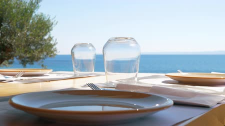 pohárek : Table with clean dishware and glasses in outdoor cafe overlooking bright blue sea Dostupné videozáznamy