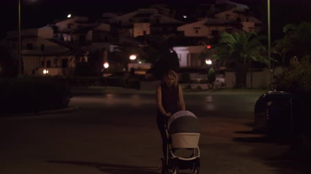 outing : Young mother having late walk with baby carriage in the neighbourhood. Outing before going to bed Stock Footage