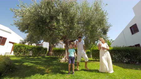 fruitful : Cheerful family of four in the garden. Dad, son and mother with baby daughter in hands dancing and having fun near big olive tree