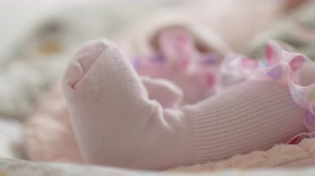 senki : Close-up shot of baby girl moving little feet in pink socks