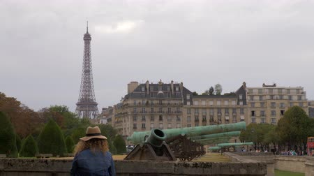 eiffel : PARIS, FRANCE - SEPTEMBER 29, 2017: Woman tourist looking at cityscape with Eiffel Tower standing near the ancient cannons at the gate of Les Invalides. Museum relating to military history of France