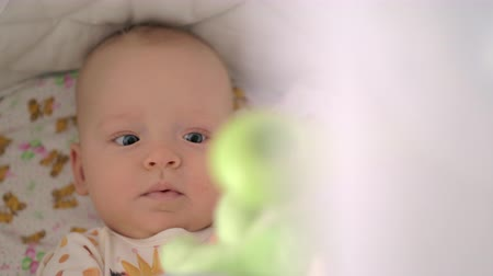 měsíců : Lovely six months baby girl lying in crib and playing with toys hanging overhead. Happy and active child