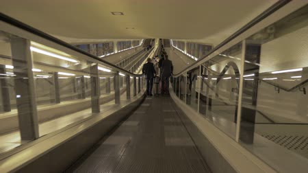 arrive : PARIS, FRANCE - SEPTEMBER 29, 2017: People with baggage riding on flat escalator through the tunnel at Charles de Gaulle Airport. The largest international airport in France and second largest in Europe Stock Footage