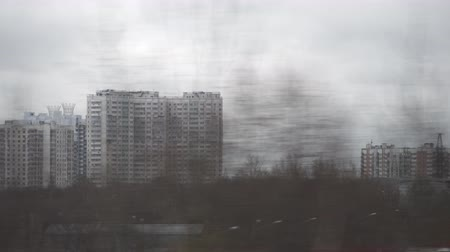 urlop : Traveling by train through Moscow and looking at apartment blocks and industrial facilities passing by, Russia