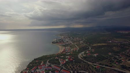 nyaraló : Aerial scene of coastal resort town Trikorfo Beach on overcast day. Sea and coast with houses, heavy clouds in the sky Stock mozgókép
