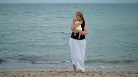 anyai : Slow motion shot of a woman looking sad and frustrated hugging and kissing baby daughter, view against the sea. Lone parent