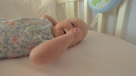 szopka : Awake newborn baby girl lying in crib at home. Child moving arms and yawning