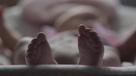 ayak parmakları : Baby girl lying in rocking chair, close-up shot and focus on little bare feet in foreground Stok Video