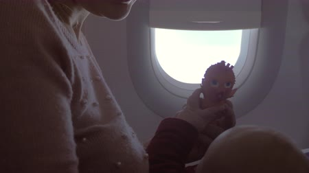 air kiss : Young mother and baby in plane. Woman playing with child and kissing beloved daughter. Family travel by plane