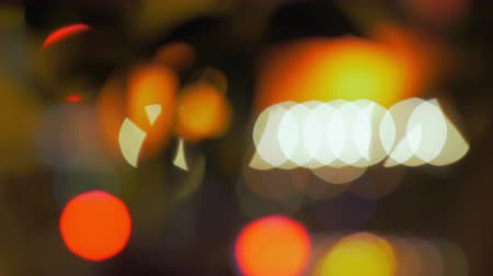 defocus : Blurred city lights and waving tree branch at night. Abstract bokeh background in white, yellow and orange colours