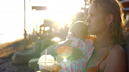 amado : Young mother with baby daughter resting at the seaside. Woman refreshing with iced drink. Enjoyable summer vacation. View against bright evening sunshine