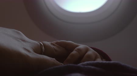 no hands : Close-up shot of mother touching little hand of baby daughter during the flight. Family air travel Stock Footage
