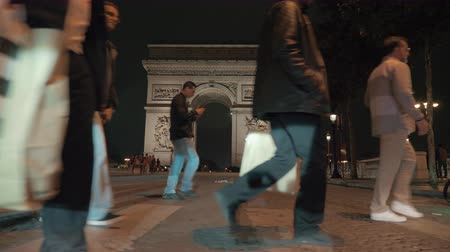 triumphal arch : PARIS, FRANCE - SEPTEMBER 29, 2017: Slow motion steadicam shot of walking across the road with other people in evening city, view to Arc de Triomphe