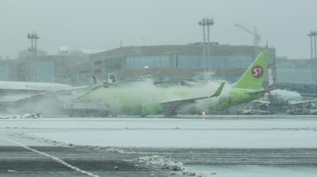 kalkış : MOSCOW, RUSSIA - DECEMBER 18, 2017: Timelapse shot of S7 Airlines airplane being de-iced before the flight on snowy winter day at Domodedovo Airport