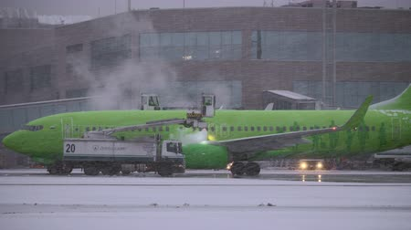 being prepared : MOSCOW, RUSSIA - DECEMBER 18, 2017: Passenger airplane of S7 Airlines being prepared for departure and deiced. Trucks spraying fluids on the aircraft at Domodedovo Airport Stock Footage