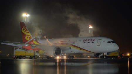 анти : MOSCOW, RUSSIA - OCTOBER 31, 2017: Slow motion shot of Boeing 787-8 Dreamliner of Hainan Airlines being de-iced before the departure from Sheremetyevo Airport at night