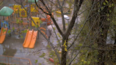 donuk : Slow motion shot of snow falling in autumn. View to the faded tree with empty children playground in the background. Unidentified woman walking with umbrella Stok Video