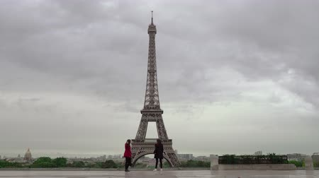 observation deck : PARIS, FRANCE - SEPTEMBER 29, 2017: Two girls at observation deck with view to the Eiffel Tower. They making video or photos with small action camera