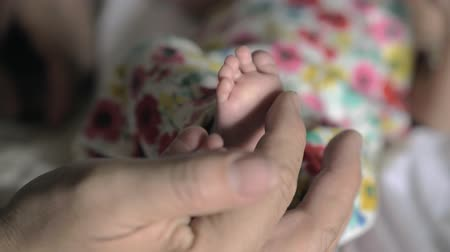 grandad : Slow motion close-up shot of grandfathers hand gently touching little feet of newborn baby