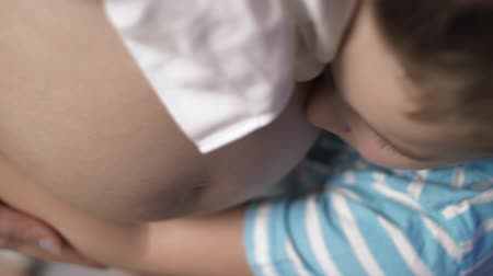 belly : Top view of boy hugging his mothers pregnant belly. Her hand is holding his arm while he is gently touching her tummy with his cheek. A moment later he is softly stroking it with his hand