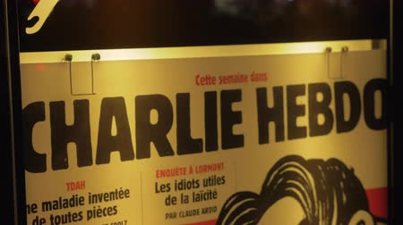 french media : PARIS, FRANCE - SEPTEMBER 29, 2017: Charlie Hebdo street banner displayed in night city. French satirical magazine, featuring cartoons, reports, polemics, and jokes Stock Footage