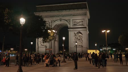 french metro : PARIS, FRANCE - SEPTEMBER 29, 2017: Citizens and tourists walking on the square near Arc de Triomphe at night Stock Footage