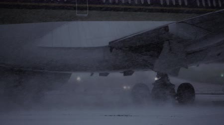 взлетно посадочная полоса : Slow motion shot of passenger airplane taxiing to runway in heavy snowfall. View to the wheels on the ground