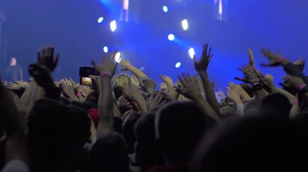 vigorous : Slow motion shot of audience enjoying the concert and dancing with hands up against stage lights