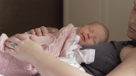 újszülött : Lovely newborn baby wrapped in pink knitted blanket sleeping soundly with mother on her chest