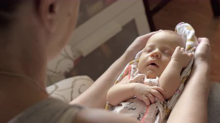 cradle : Grandma lulling baby granddaughter to sleep rocking her on the lap. Grandparent babysitting Stock Footage