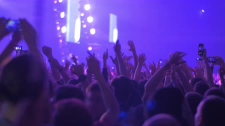 vigorous : Crowd of fans dancing to dynamic and rhythmic music at the concert, some people making mobile videos. View with stage lights