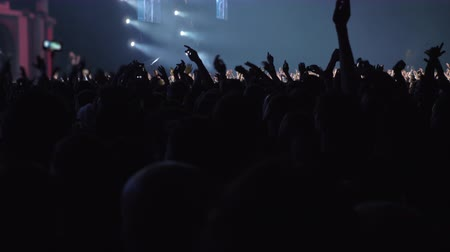 concert hall : At the concert. Crowd of unidentified music fans raising hands and dancing, colored stage lights blinking
