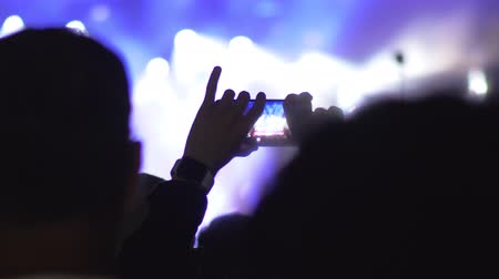 película de filme : One man in the crowd of excited music fans taking video of the concert with smart phone Stock Footage