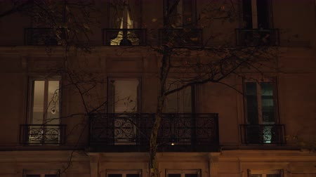 çok katlı : PARIS, FRANCE - SEPTEMBER 29, 2017: Night view of the house and bare autumn tree in dim light of street lantern, people can be seen in the windows