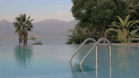 bóia : A beautiful day near the open swimming pool. The water surface is clear and quite. The railing is shining in the middle of it. Behind the pool there are some bright green palm trees and other plants. On the background we can see beautiful high mountains b