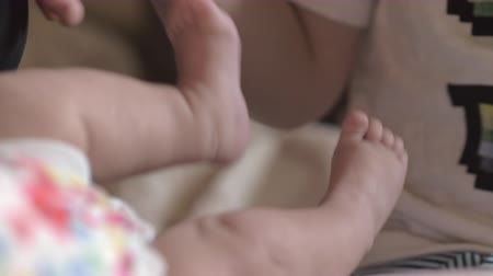 ジュニア : Close-up shot of elder brother looking after newborn baby sister and carefully touching her small feet 動画素材