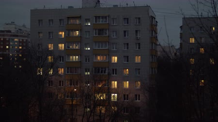 çok katlı : View to apartment block in the dusk. Lights in the windows, bare trees in the yard