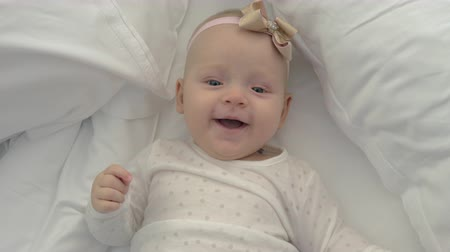 měsíců : An adorable baby girl is lying on a bed on white sheets. She is laughing happily. A pink and golden bow on her head and a polka dots blouse are making her even cuter Dostupné videozáznamy