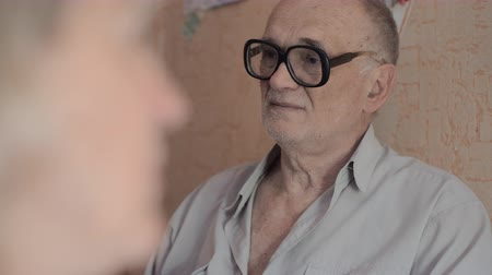 grandad : Senior man in glasses at home. He talking to family members and listening to their conversation Stock Footage