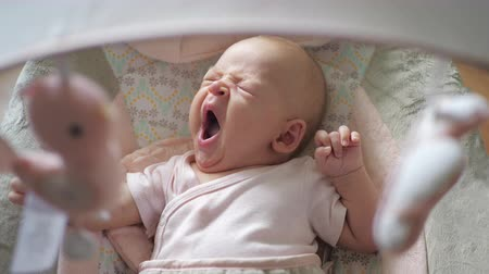 szopka : Slow motion shot of two months old baby girl rocking in bouncy seat. Child yawning and looking at toys hanging overhead Wideo