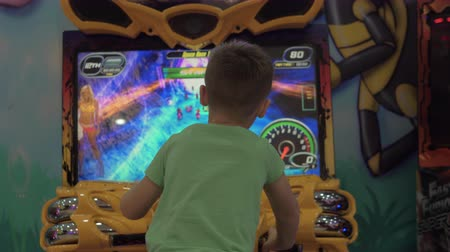 arcada : ANTALYA, TURKEY - NOVEMBER 11, 2017: Back view of the boy (with model release) playing motorcycle racing simulator in indoor amusement park