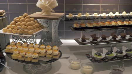 kuchařství : A beautiful view on a long dessert buffet. There are numerous kinds of different cakes, cookies and other desserts, nicely decorated and served