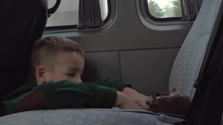 еж : Boy playing with toy hedgehog and crocodile when traveling in minivan Стоковые видеозаписи
