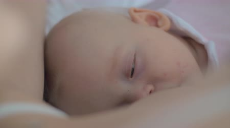 mesi : A close up of a baby girls sleepy face. A six months old baby is almost sleeping while a mother is breastfeeding her