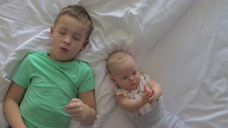 rodzeństwo : Top view of seven years old boy with junior baby sister of six months lying on bed together