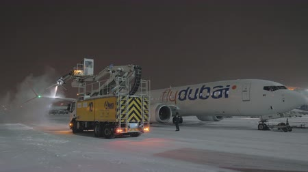 анти : MOSCOW, RUSSIA - JANUARY 29, 2018: Passenger airplane Flydubai Boeing 737-8 MAX being de-iced before night departure from Sheremetyevo Airport Стоковые видеозаписи