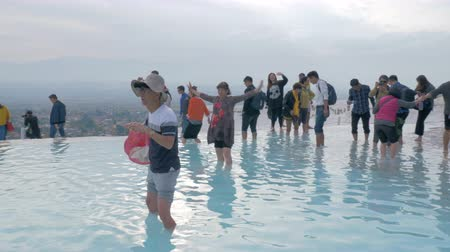 tourist sight : PAMUKKALE, TURKEY - NOVEMBER 13, 2017: Many tourists walking barefoot in travertine terraces with hot water springs. Visiting natural landmark
