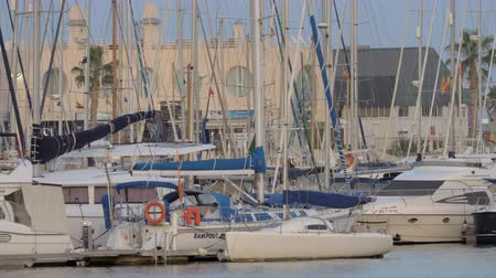 пирс : ALICANTE, SPAIN - APRIL 19, 2018: Many yachts moored in city quay, Spanish flag on vessels flattering in the wind
